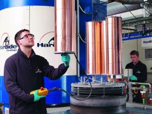 Ein Mitarbeiter belädt den Reaktor mit Kupfer-Bauteilen, um sie zu beschichten und damit ihre Oberfläche zu härten. (Bildquelle: Hardide)