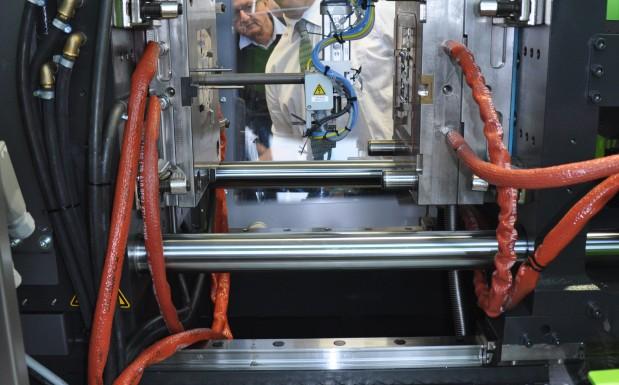 Der Robotergreifer fährt in die Form und legt das Rohmaterial in die Induktionsspule ein, damit diese es verflüssigt.  (Bildquelle: David Löh/Redaktion Plastverarbeiter)