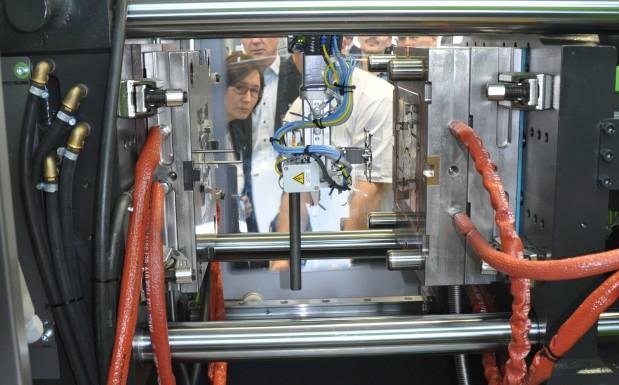 Der lange Fortsatz des Greifers ist die Haltevorrichtung für das Rohmaterial. Damit nimmt der Roboter, ein Engel Viper 6, die Liquid-Metal-Stange aus dem Förderer und führt sie durch die feststehende Werkzeugplatte in die Induktionsspule.  (Bildquelle: David Löh/Redaktion Plastverarbeiter)