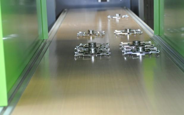 Fertige Demoteile aus der Liquid-Metal-Legierung LM105. Sie wurden gerade abgelegt und fahren jetzt durch das Gebläse in Richtung Kiste.  (Bildquelle: David Löh/Redaktion Plastverarbeiter)