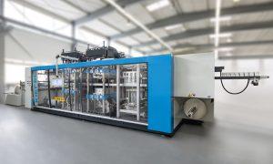 Der Druckluftformautomat produziert von der Folienrolle ab fertig in Beutel eingepackte Domdeckel mit Trinkhalmloch.