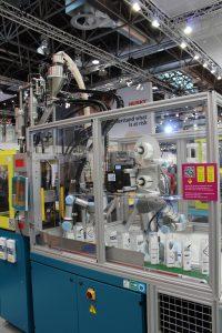 Die Spritzgießmaschine von Dr. Boy produziert einen Kunststoffbecher, den einer der beiden integrierten kollaborierenden Roboter, ein UR3 und ein UR5, entnimmt. (Bildquelle: Dr. Boy)