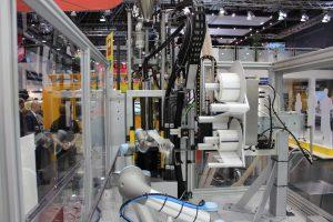 Einer der zwei integrierten kollaborierenden Roboter, ein UR3 und ein UR5, führt den Becher einem Etikettendrucker zu, der ihn mit den eingegebenen Daten und dem daraus generierten QR-Code bedruckt. (Bildquelle: Dr. Boy)