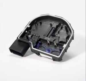 Die Getriebedeckel für Frontwischeranlagen bestehen aus drei Komponenten: Das Hauptmaterial ist mit dreißig Prozent Glasfaser versetztes PBT. Dazu kommen eine weiße und eine blaue TPE-Dichtung.  (Bildquelle: Hekuma)
