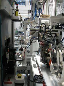 Den letzten Schritt des Produktionsprozesses der Getriebedeckel bildet die Montage der Druck-Ausgleichs-Membrane. Diese führt zunächst eine Haspel mit Papieraufwicklung zu. Dann wird sie gestanzt und mittels eines Pick-and-Place-Systems in die Fertigteile eingelegt und in der Laserschweißstation verschweißt.  (Bildquelle: Hekuma)