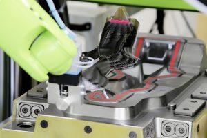 Der HP-RTM-Prozess startet mit dem automatisierten Einlegen des vorgefertigten Preforms durch einen Roboter. Dieser entnimmt das Bauteil dann auch nach dem 125-sekündigen Aushärte-Prozess. (Bildquelle: Hennecke)