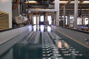 Blick in die vollautomatische Spritzgussproduktion bei Kläger mit dem Teile-Fließband im Vordergrund (Bildquelle: Kläger)