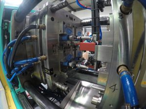 Weil die Verschlussmechanismen spiegelverkehrt aufgebaut sind, muss der Greifer die unteren zwei Kappen während der Zufuhr um 180 Grad drehen.