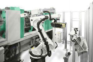 Das FDC-Verfahren lässt sich auch mit Organoblechen kombinieren. In diesem Beispiel wurde der Verfahren mit einem Sechs-Achs-Roboter automatisiert. Dabei werden die Organobleche bereits im Greifer vorgeheizt. Dieser schwenkt sie dann vor einen Infrarot-Heizstrahler bis die festgelegte Umformtemperatur erreicht ist, und legt sie schließlich in das Werkzeug ein. (Bildquelle: Arburg)