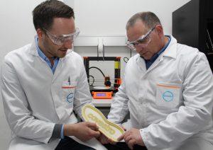 Schuhsohle mit aufgedrucktem Klebstoff. Im Hintergrund ist ein Drucker nach dem Schmelzschichtverfahren  zu sehen. (Bildquelle: Covestro)