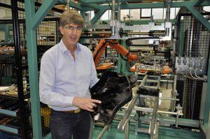 Gunter Maus, Vertriebsleiter bei Bielomtaik Leuze, zeigt die spritzgegossene Halbschale, die der Sechsachs-Roboter im Hintergrund durch den Fertigungsprozess inklusive Heizelementschweißen führt. (Bildquelle: David Löh/Redaktion Plastverarbeiter)