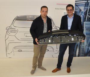 Michael Wurdack (l.), Rehau, und Wolfgang Breu, Knur, präsentieren den Heckspoiler, den die gemeinsam entwickelte 2K-Hybrid-Klebeanlage produziert. (Bildquelle: David Löh/Redaktion Plastverarbeiter)