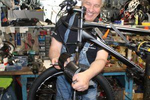 Gabriel Kenzel in seiner Fahrrad-Werkstatt mit seinem 'Flexi-Carbon'-Schutzblech. Beim Einstieg in die Serienproduktion hilft ihm das Augsburg Center for Entrepreneurship der Universität Augsburg. (Bildquelle: G. Kenzel)