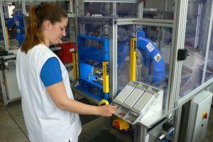 Eine Werkerin setzt zunächst die Hauptkomponenten des Ventils ein. Nachdem der Roboter anschließend die Kleinteile eingelegt hat, gibt sie das Signal zum Zusammenpressen der Teile.