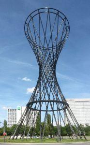 Das nach der Schauspielerin Mae West benannte Kunstwerk (2011) in München: Eine 52 m hohe Plastik aus Rohren – überwiegend aus CFK – in Form eines Rotationshyperboloids. (Bildquelle: Wikipedia commons/M(e)ister Eiskalt)