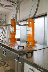 Zur Materialversorgung wird das Rohmaterial von Materialabscheidern zuerst in große Tagesbehälter gefördert und von hier aus über einen Kupplungsbahnhof auf die einzelnen Spritzgießgießmaschinen verteilt. (Bildquelle: Werner Koch)