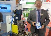Dr. h.c. Wolfgang Leonhardt präsentiert seine horizontalen Kniehebelmaschine aus dem Jahr 1976 und die damit produzierten Chips mit Hologrammen. (Bildquelle: Simone Fischer/Redaktion Plastverarbeiter)