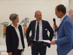 Sandra Füllsack und Carl Litherland von der Motan Holding im Gespräch mit T. Kühnmann. (Bildquelle: Simone Fischer/Redaktion Plastverarbeiter)