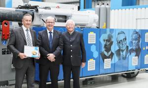 Tradition und Moderne vereint: Marcus Wirthwein, Dr. Hans Ulrich Golz und Udo Wirthwein vor der Jubiläumsmaschine (v.l.). (Bildquelle: Krauss Maffei)