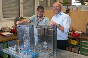 Der Konstrukteur Alexander Brock und der Werkzeugbauer Frank Vollmer mit den beiden Hälften des Werkzeugs für die Entriegelungsgriffe aus Polypropylen, die damit im Spritzguss hergestellt werden. Vorn im Bild die hellblauen Entriegelungsgriffe.