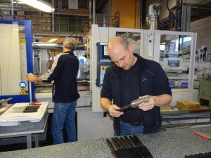 Björn Mutschler bei der Qualitätskontrolle eines frisch gespritzten Tortenmessers. Im Hintergrund werden bereits die nächsten Klingen – 1x Tortenmesser, 2x Stechmesser – in die Form eingelegt. Angespritzt wird ein Griff aus PP20GF.