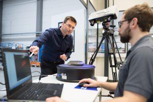 Für das Reverse Engineering scannen Abteilungsleiter Dr. Roman Lengsdorf (l.) und sein Mitarbeiter (r.) das Bauteil – eine alte Vespa-Stoßstange – auf dem Rundtisch mit einer Stereokamera. (Bildquelle: Zeiss IMT)