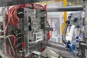 Die Duo 700 Maschine ist für die Dreikomponentenfertigung der Mittelkonsolen mit einem Drehteller ausgerüstet: Ein Knickarmroboter entnimmt die Spritzgießteile. (Bildquelle: Engel)