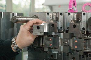 Dieser Schieber entspricht in etwa dem des Testobjekts und ist Bestandteil eines Mehrkavitätenwerkzeugs. Damit werden Kunststoffbügel gespritzt, die als Verriegelung des bekannten, modular aufgebauten Han-Steckers dienen. Die Toleranzvorgabe für alle Flächen beträgt zwischen 0 mm und -0,01 mm im Gesamtmaß.