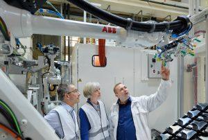Andreas Dak erläutert Jürgen Schwarz, SAR Group, und Simone Fischer, Plastverarbeiter, das Greiferkonzept für die Black-Panel-Bauteile. (Bildquelle: SAR)