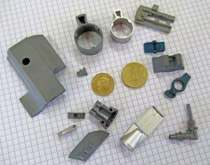 Eine Auswahl typischer MIM-Teile in verschiedenen Fertigungsstadien vom spritzgegossenen Grünteil über das Braunteil (nach dem Entbindungsprozess) bis zum fertig gesinterten MIM-Teil. (Bildquelle: Klaus Vollrath)