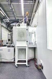 Die Spritzgießmaschine befindet sich im Schwarzbereich des neuen Produktions- und Logistikzentrums. Sie lässt sich jedoch vom Reinraum aus be- und entladen. Für den Spritzbereich wurde eine horizontal strömende Filter-Fan-Unit (FFU) an das Gehäuse der Maschine als Schutzzone angebaut, damit sich die Bauteile stets unter Reinraumbedingungen befinden.