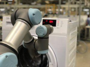 Die Funktionsprüfung der fertigen Waschmaschine ist zum größten Teil automatisiert. Von Mitarbeitern werden lediglich die Drehknöpfe geprüft, da Maschinen deren Haptik (noch) schwer bewerten können. (Bildquelle: Krauss Maffei)