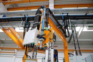 Über 200 Meter blaue Leitungsrohre durchziehen die Montagehalle. Über schwenkbare Kragarme werden die Medien Druckluft, Kühlwasser und Starkstrom flexibel den Montageplätzen der Maschinen zugeführt.