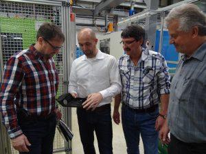 Stefan Centmayer erläutert seinen Kollegen die in den Haltearm des Spiegelersatzsystems integrierten Funktionen. (Bildquelle: Simone Fischer/Redaktion Plastverarbeiter)