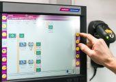 Touchscreen-Netzwerksteuerung. Rechts davon ein an der Wand montierter Barcode-Scanner. Die Steuerung überwacht den Materialfluss von der Materialquelle bis zur Verarbeitungsmaschine. (Bildquelle: Wittmann)