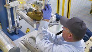 Ein BASF-Mitarbeiter nimmt an einer Gusbi-Maschine einen Schuh aus der Form. (Bildquelle: BASF)