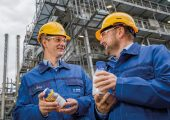 Dr. Stefan Gräter und Dr. Andreas Kicherer zeigen eine Probe von Pyrolyseöl und damit hergestellten Kunststoff vor dem Steamcracker. (Bildquelle: BASF)