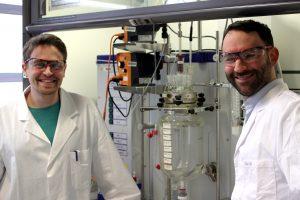 Die beiden Autoren Paul Stockmann (links) und Daniel Dr. Van Opdenbosch mit dem Reaktor, in dem das polymerisationsfähigen Monomer aus dem Naturstoff 3-Caren hergestellt wurde. (Bildquelle: Prof. Cordt Zollfrank / TUM)