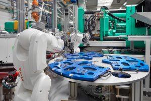Roboter im Einsatz: Die 6-Achser legen zu umspritzende Schrauben in Gehäuseteile. (Bildquelle: Arburg)