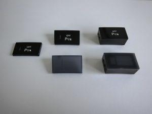 Fertigungsstufen eines herkömmlichen Schalters. Vorgeformte Folie, mit PC transluszent grau hinterspritzt und mit funktioneller Komponente aus PC/ABS (von links, oben). Die beiden unteren Teile zeigen die Fertigungsstufen ohne IML-Folie. (Bildquelle: KH Foliotec)