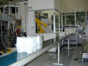 Die fertig montierten Kunststoffboxen (in Folie eingeschweißt) laufen auf einem offenen Förderband aus dem Reinraum in die Verpackung. (Bildquelle: alle Colandis)