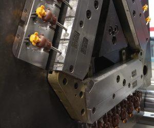 65 t Werkzeug mit drehender Indexplatte, in das über einen Heißkanal (31 Zonen) die drei unterschiedlichen Werkstoffe eingespritzt werden. Kopf PBT, Rumpf PA6GF35 und Arme und Beine aus POM. (Bildquelle: Geobra Brandstätter)