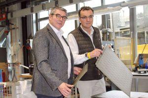 Dirk Wevelsiep, Vertriebsleiter ErgoTek, zeigte Thomas Bertram, Vertrieb Wittmann Battenfeld, die neue Produktentwicklung, eine Bodenplatte mit selbstabdichtendem Hinterschnitt. (Bildquelle: Wittmann Battenfeld)