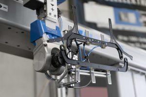 Automatisierung mit Greiferlösung zur Entnahme des fertigen Bauteils, das aus einem Träger mit zwei Kopfbändern und einem Visierträger besteht. (Bildquelle: Haimer)