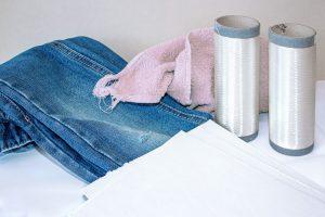 Das aufgespulte Viskosefilamentgarn wurde aus recycelter Baumwolle gefertigt, die in Form von Zellstoffplatten vorliegt. Forscherinnen und Forscher am Fraunhofer IAP haben einen Weg gefunden, aus Baumwollkleidung wie Jeans hochwertige neue Kleidungsstücke herzustellen, anstatt wie bisher nur Putzlappen. (Bildquelle: Fraunhofer IAP)