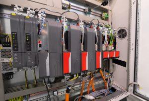 Der Schaltschrank beherbergt  die Antriebsregler für die Servoachsen. Links daneben sind die PES-Module angeordnet.