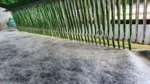 Im Betrieb der Tuftingmaschine am TFI stechen die Nadeln in das Trägermaterial und bringen so das Polgarn für den Kunstrasen ein. (Bildquelle: TFI)