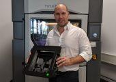 Stefan Kammann,  Head of Samples and Mechanical Solutions, Continental Engineering Services, vor dem Fortus 450mc 3D-Drucker im ADaM Competence Center mit einer 3D-gedruckten, ESD-konformen Klebevorrichtung. (Bildquelle: Stratasys)