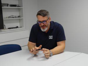 Vertriebsleiter Antonio Trinchese erläutert an einem Bauteil die Herausforderungen des Projekts. (Bildquelle: Simone Fischer/Redaktion Plastverarbeiter)
