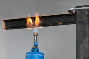 Brandtest an einem Modellträger. Das schwarze Trägerprofil besteht aus einem der neuen Typen, die Verrippung aus einem orangenen, ebenfalls halogenfrei flammgeschützten Polyamid 6. Die Flammen breiten sich nicht aus, sondern erlöschen nach Entfernen des Brenners, unabhängig davon, ob der Träger flächig oder an den Kanten beflammt wird. (Bildquelle: Lanxess)